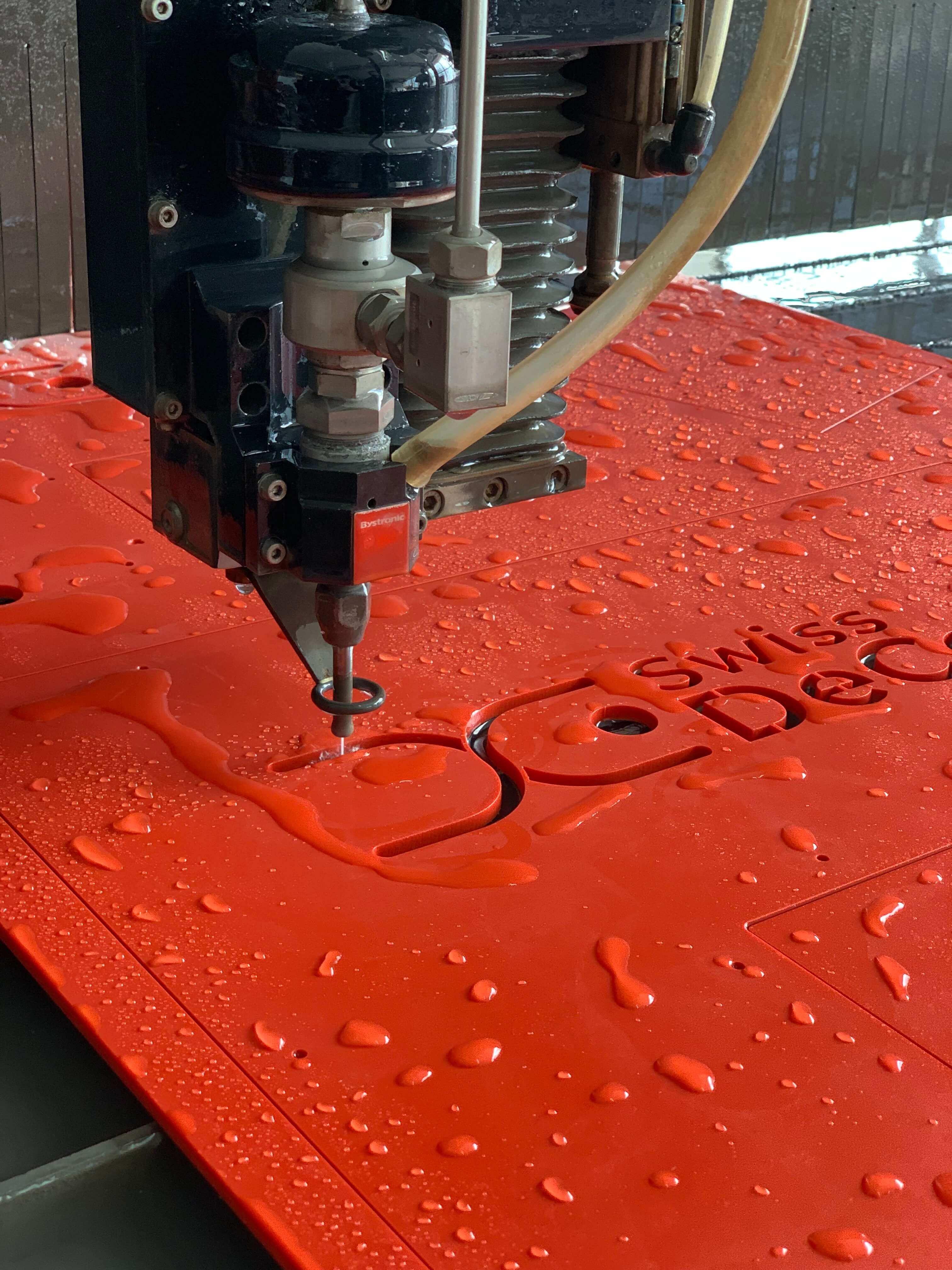 Découpage jet d'eau d'une enseigne en plastique rouge